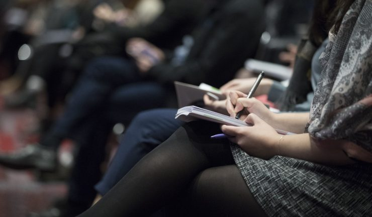 people sit on chairs at a conference taking notes