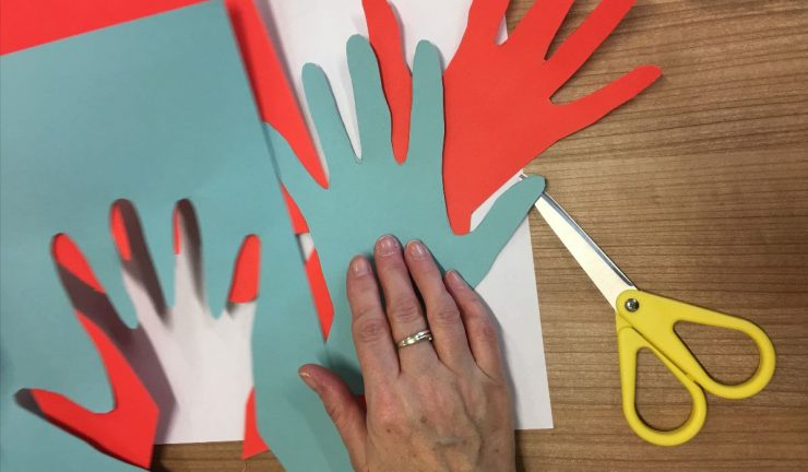 Someone cuts out hand shapes from coloured paper