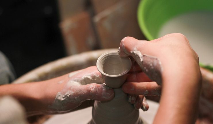 Person making ceramics on a pottery wheel