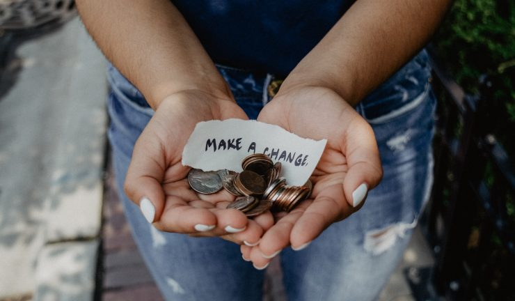person's hands holding coins and a paper note that says 'make a change'